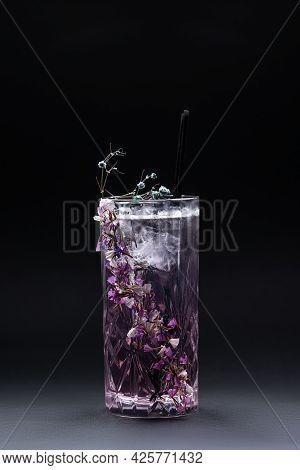 Luxury Violet Fizz Cocktail Drink With Flower Decoration On Black Background