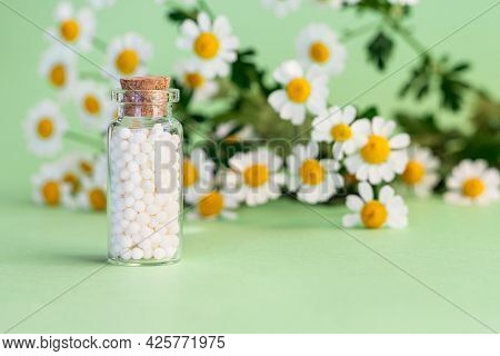 Classical Homeopathy Globules In Vintage Bottle On Background Of Fresh Chamomile Flowers. Alternativ
