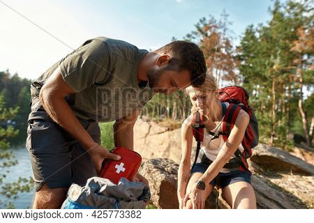 Young Caucasian Man Using First Aid Kit On Injured Leg Of Woman Sitting On Rock During Hiking In Sum