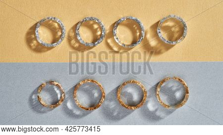 Clear Resin Rings With Golden And Silver Filling Lying Flat In Row On Gray Orange Background, Widesc