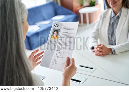 Female Hr Manager Holding Cv At Job Interview At Desk, Over Shoulder View. Employer Checking Reading