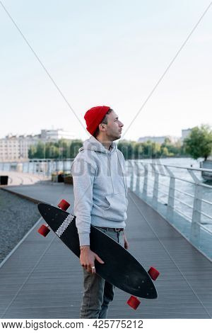 Casual Guy With Longboard On City Bridge Skating After Sunset In Urban Space. Trendy Millennial Man