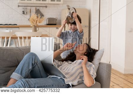 Annoyed Young Mom Ask Son To Calm Down Try To Concentrate On Work. Small Kid Disturb Millennial Moth