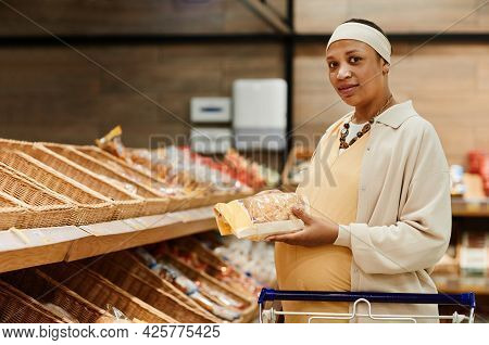 Waist Up Portrait Of Pregnant African-american Woman Buying Fresh Bread While Grocery Shopping In Su