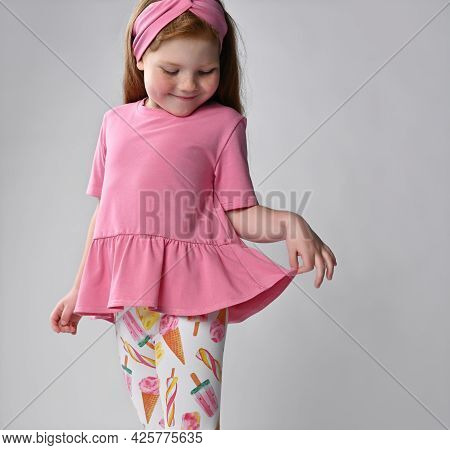 Small Red-haired Girl Touching Dress, Looking At Clothes, Showing Views Of Summer Fashion. Advertisi