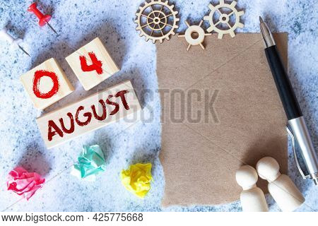 August 4. Date Of August Month. Number Cube With A Flower And Notebook On Diamond Wood Table For The