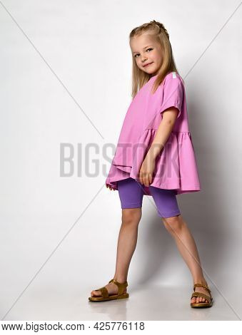 Cute Little Girl Standing In A Blouse With A Fuchsia Peplum And Legends On A Light Background In The
