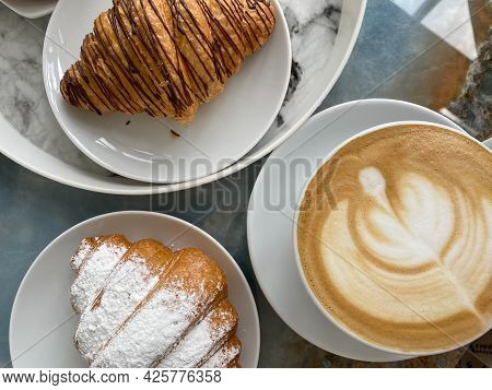 Two Delicious Croissants And A Cup Of Invigorating Cappuccino On The Table Close-up