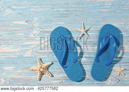 Blue Beach Rubber Flip Flops And Starfish On A Blue Wooden Background, View From Above