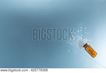 Homeopathic Pellets Are Scattered From A Glass Jar On A Blue Surface.