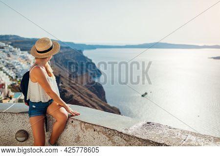 Woman Tourist Enjoying Caldera Sea Landscape In Fira, Santorini Island Looking At Seaside And Mounta