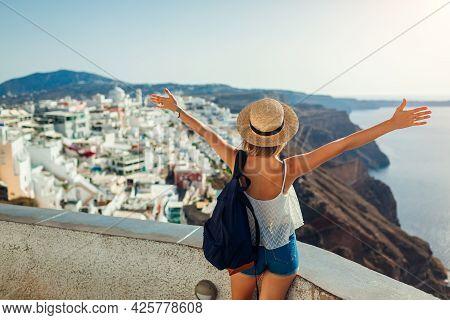 Woman Tourist Raised Arms Looking At Caldera Sea Landscape In Fira, Santorini Island. Traveling Duri