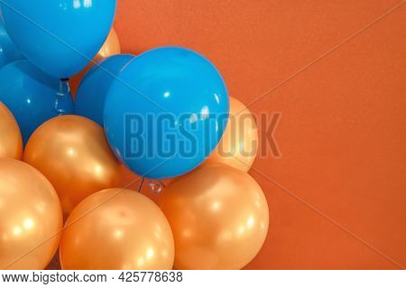 Blue And Orange Holiday Balloons Decor The Interior On A Brown Background, Copy Space Or Place For T