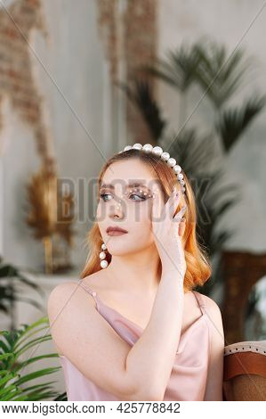 Portrait Of A Young Beautiful Woman With Makeup Made Of Mother-of-pearl Pearls On Her Face And Hand
