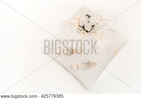 Wedding Rings Of Newlyweds On A White Decorative Pillow On A Light Background.