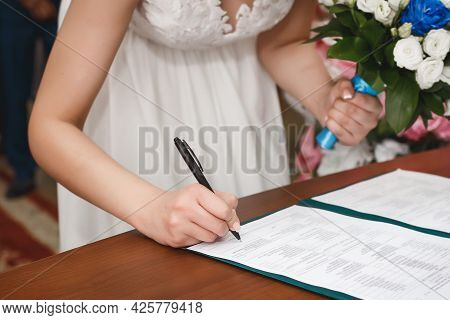 The Hand Of A Young Girl Bride At The Wedding Puts The Signature Of Consent To Marriage In The Docum