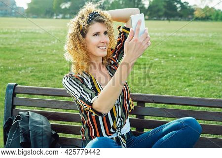 Curly Hair Woman Making Selfie Photo On A Mobile Phone. Stylish Happy Smiling Woman In Striped Multi