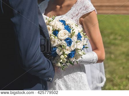 The Bride And Groom In A White Dress Stand Next To Each Other Hugging, Holding A Wedding Bouquet Of