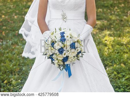 Bride In White Wedding Dress Holds A Bouquet Of Flowers White And Blue Roses Close Up.
