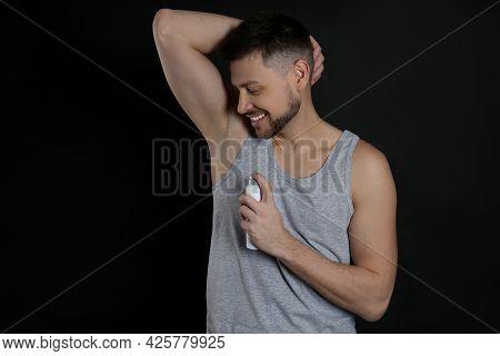 Handsome Man Applying Deodorant On Black Background