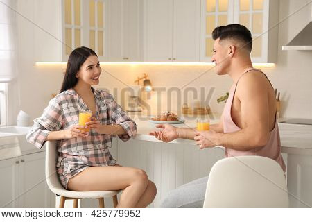 Happy Couple Wearing Pyjamas During Breakfast At Table In Kitchen