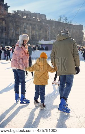Family Spending Time Together At Outdoor Ice Skating Rink, Back View
