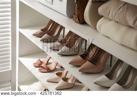 Stylish Women's Shoes, Clothes And Bags On Shelving Unit In Dressing Room