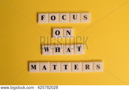 Square Letters With Text Focus On What Matters Isolated On Yellow Background.