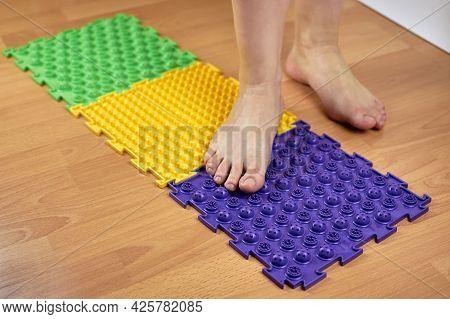 Orthopedic Massage Mat. Women\'s Feet Standing On An Orthopedic Mat. Prevention Of Flat Feet.