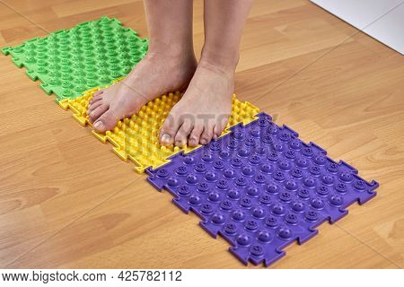 Orthopedic Mats For The Prevention Of Flat Feet. Women\'s Feet Standing On An Orthopedic Mat. Feet A