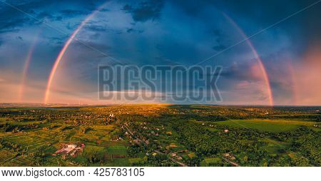 A Huge Double Rainbow After Rain Over A Small Town Among The Fields. A Unique Atmospheric Phenomenon