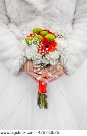 Bride In White Coat And Wedding Dress Holds A Bouquet Of Flowers.