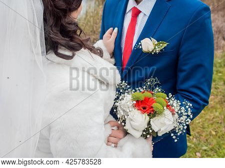 The Bride In A Veil In A White Coat Stands Opposite The Groom In A Blue Suit, Red Tie And White Shir