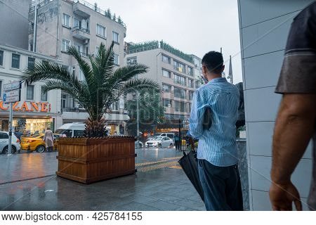 Beyoglu, Istanbul, Turkey - 06.18.2021: A Male Person Standing In Front Of A Column Of Building Whil