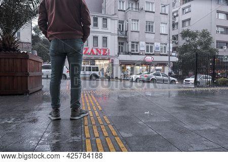 Beyoglu, Istanbul, Turkey - 06.18.2021: Low Angle View Of A Turkish Man Standing Near Rainy Street W