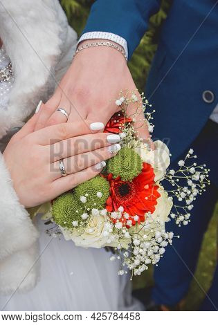 Bride In White Coat Put Her Hand On The Hand Of The Groom On The Wedding Bouquet Of Flowers, Close-u