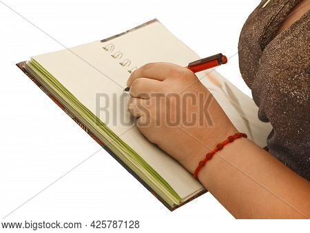 The Girl's Hand Holds A Pen And Writes In A Notebook Place For Text And Design Close-up.