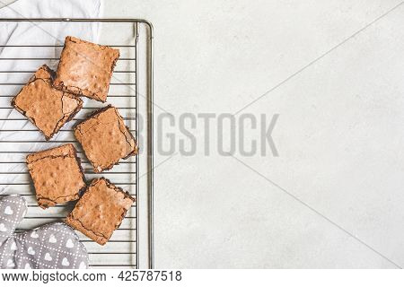 Top View Of Freshly Baked Home Made Brownie Cake Cut In Squares Over A Backing Rack. Copy Space.