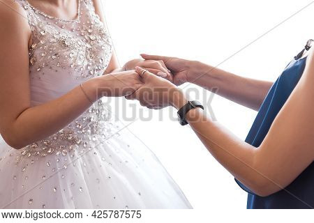 Mom And Bride In White Dress Hold Hands, Close-up.