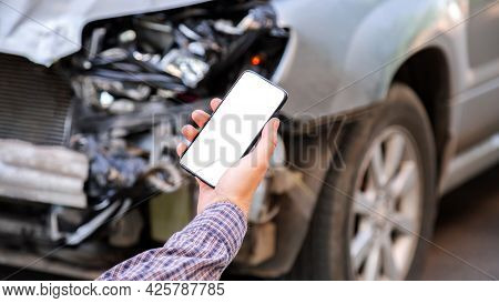 Man Holds Mockup Mobile White Phone Screen In Hands After Car Accident. Calling Insurance Service In