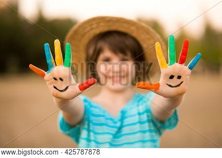 Happy Smiling Little Girl With Hands In Painted In Funny Face Play Outdoor In Summer Park. Focus On