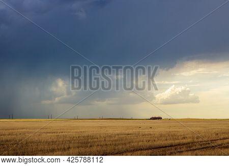 Dark Storm Clouds Over The Horizon With Heavy Rain On A Windswept Prairie, Sunlight, And A Farm Hous