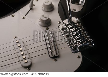 Black And White Electronic Guitar Close Up View. Details Of Rock Guitar. Strings, Tremolo And Volume