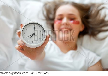 Happy Young Woman Wake Up After Sleeping Holding Bed Side Alarm Clock In Hand. Morning Beauty Routin