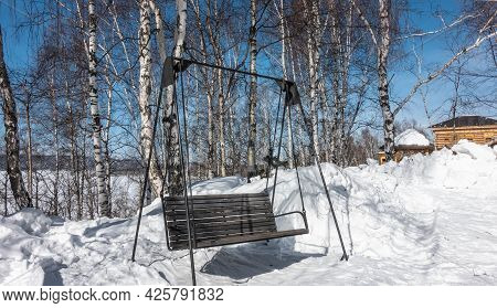 Swing - A Bench Made Of Unpainted Boards Suspended On Metal Supports. Snowdrifts Around. In The Dist