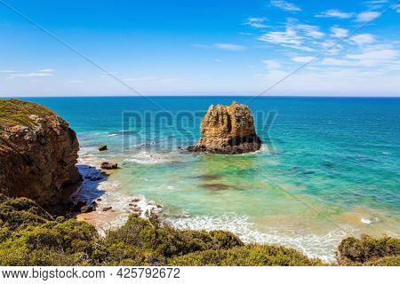 Pacific coast and sandy beach. Travel to the Southern Hemisphere. Fabulous journey to Australia. Alumina residues - cliffs  in the snow-white foam of the ocean surf.