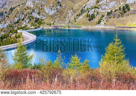 The grand dam raises the water level in the lake. Lago di Fedaya. Mount Marmolada. Italy, Dolomites, Fedaya pass. Travel to the land of lakes and mountains