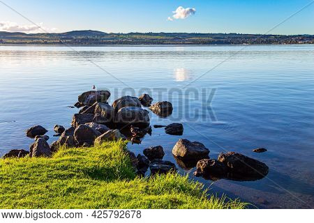Warm evening on the lake. Magnificent sunset. New Zealand. The largest Lake Taupo. The magnificent lake is a popular holiday destination for tourists.