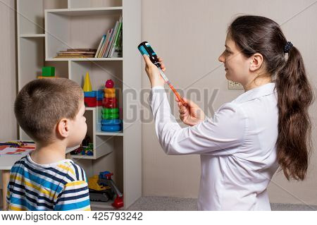 The Doctor Picks Up From The Bottle A Sprinkle Of Cough And Temperature For Children In A Measuring