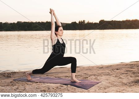 A Woman Practices Yoga While Standing In The Position Of Warrior 1 Or Virabhadrasana One. Yoga At Su
